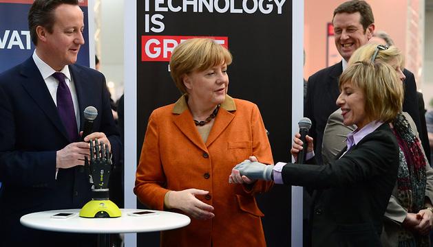 El primer ministro británico, David Cameron, y la canciller alemana, Angela Merkel (centro), observan el funcionamiento de una mano biónica en la feria CeBIT en Hannover