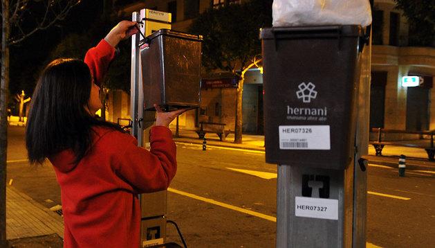 Una mujer coloca un cubo de basura en un enganche del 'puerta a puerta' en Hernani (Guipúzcoa).