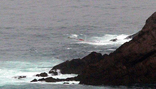El casco del barco asoma entre las rocas.