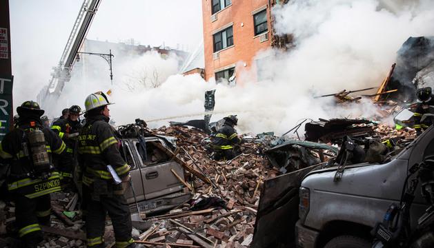 Los bomberos entre los restos de la explosión
