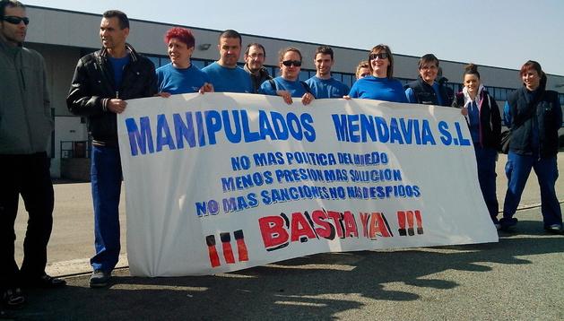 Un grupo de trabajadores de la empresa con la pancarta