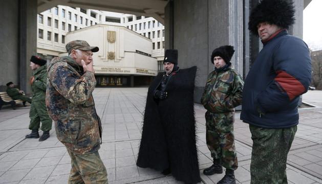 Varios cosacos vestidos con el traje y el gorro tradicional hacen guardia a las afueras del edificio del Parlamento regional en Simferópol, Crimea, este miércoles