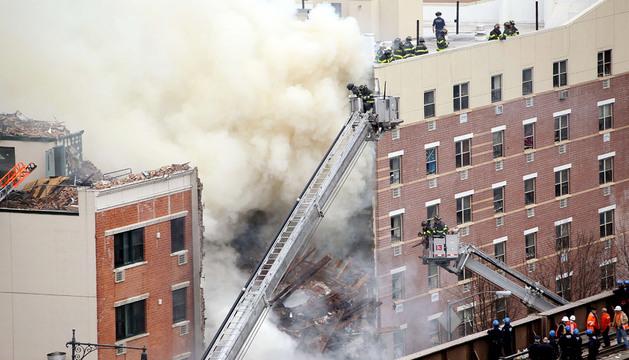 Bomberos trabajan en las labores de extinción del incendio provocado por la explosión de gas.