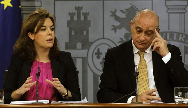 La vicepresidenta del Gobierno, Soraya Sáenz de Santamaría, junto al ministro del Interior, Jorge Fernández, durante la rueda de prensa tras la reunión del Consejo de Ministros.