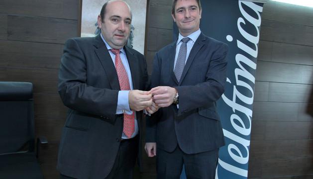 Juan Carlos González Muñoz (izda), alcalde de Burlada, sujeta un cable de fibra óptica junto al director de Telefónica en Navarra, Roberto Mercero Igoa