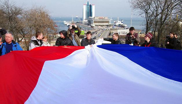 Un grupo de personas lleva una bandera de Rusia