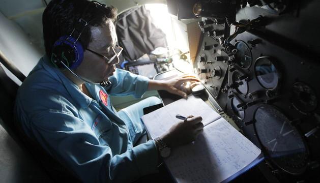 Un militar vietnamita toma notas en un avión de las Fuerzas Aéreas vietnamitas durante una operación de búsqueda del vuelo MH370 de Malaysian Airlines