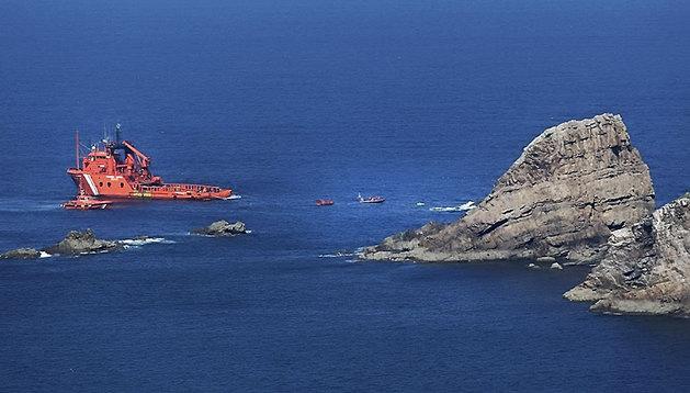 Un grupo de buzos y una embarcación de Salvamento Marítimo trabajan en el rescate de los cuatro tripulantes aún desaparecidos tras el naufragio el pasado lunes del pesquero Santa Ana, a media milla del Cabo Peñas.
