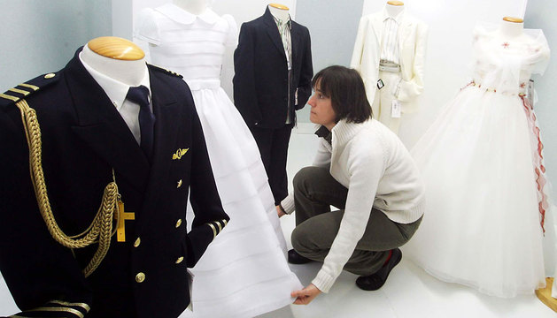 Una dependienta coloca unos vestidos y trajes de Primera Comunión.