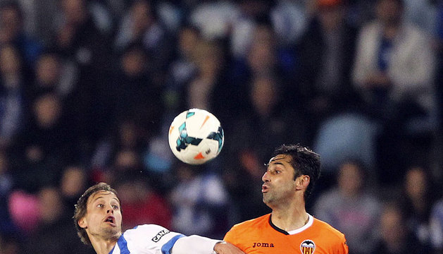 El centrocampista de la Real Sociedad Sergio Canales (i) lucha un balón con el centrocampista Daniel Parejo, del Valencia.