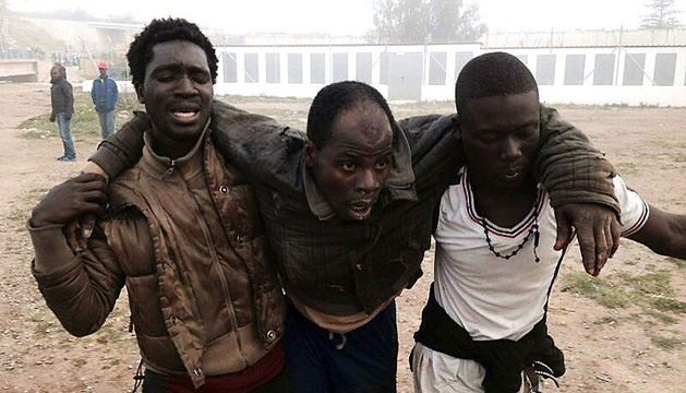 Uno de los inmigrantes herido es auxiliado por dos de sus compañeros.