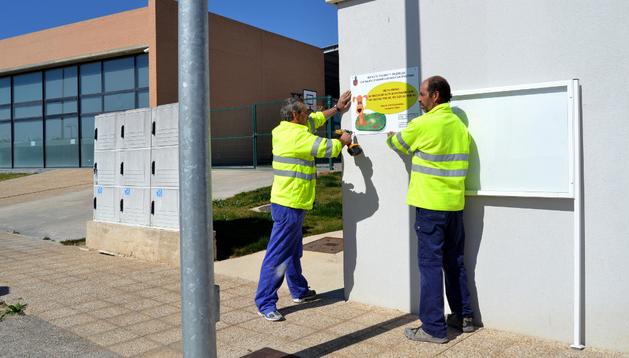 Dos trabajadores colocan un panel junto al complejo deportivo