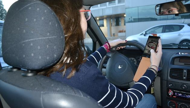 Una mujer al volante mientras mira el móvil