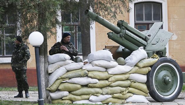 Soldados ucranianos vigilan junto a vehículos blindados en la base naval de Simferópol, capital de Crimea, el 19 de marzo del 2014