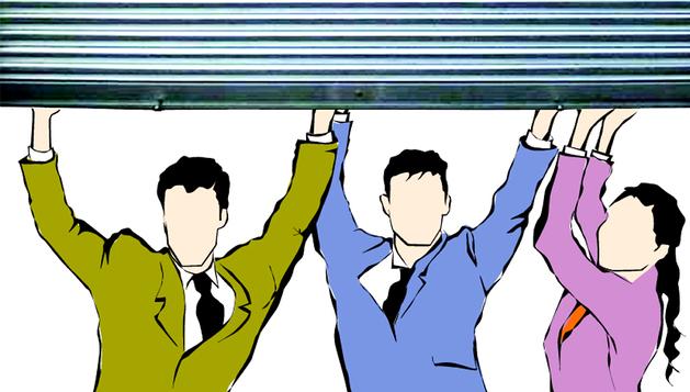 Tres personas levantan la persiana de un negocio