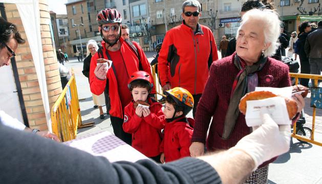Dos niños y varios adultos degustan las randillas con las que les obsequió la Orden del Volatín