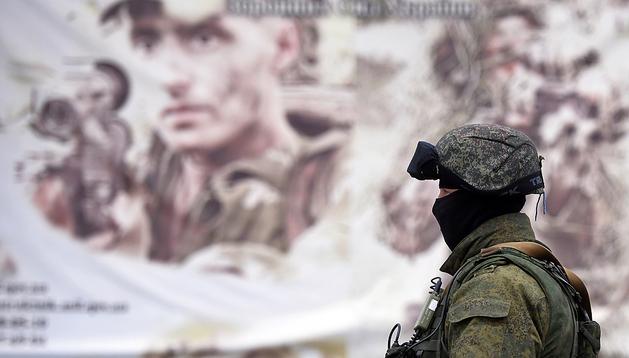 Un soldado ruso mont guardia ante un cartel de reclutamiento ucraniano en la localidad de Perevalnoye