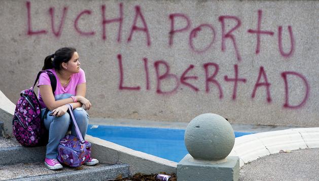 Una mujer observa en la Plaza Altamira de Caracas mientras manifestantes protestan contra el gobierno de Nicolás Maduro