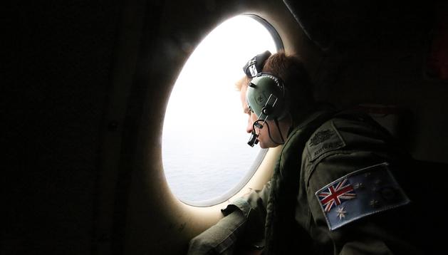 Un militar de la Royal Australian Air Force busca desde un AP-3C Orion restos del avión desaparecido