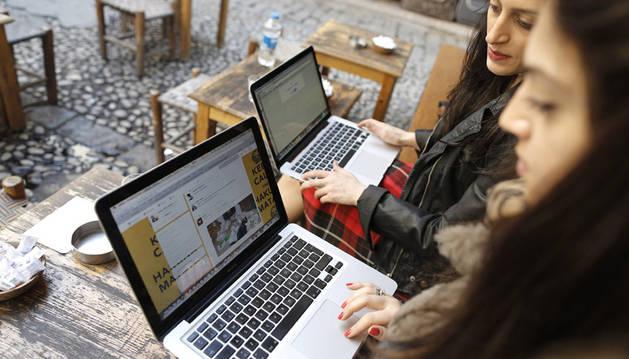Dos mujeres intentan conectarse a Twitter desde sus portátiles en una cafetería en Estambul.