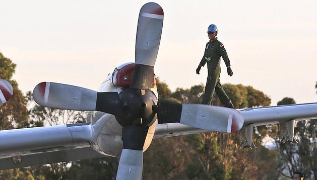 Un soldado camina por encima de un avión japonés en Perth
