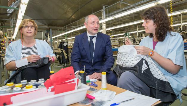 José Carlos Fernández, gerente de Segura Taylor, en la fábrica, junto con las forradoras de los trajes Agustina Flores (izda) y Gema Bravo
