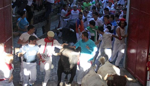 Dos mozos tocan a un toro en el callejón.