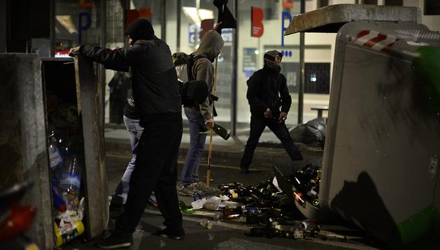 Varios jóvenes se parapetan tras unos contenedores con botellas en la mano durante los actos violentos en Barcelona