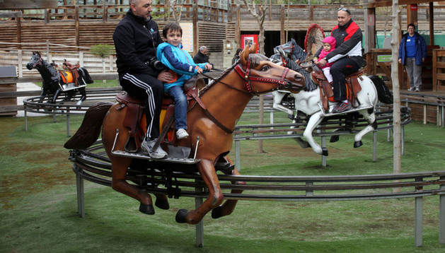Adultos y niños montan en un carrusel de caballitos