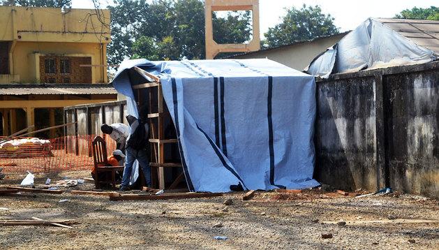 Unos trabajadores montan una caseta para aislar a los enfermos