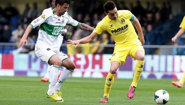 El centrocampista del Villarreal Bruno Soriano controla el balón ante el centrocampista del Elche, Javi Márquez