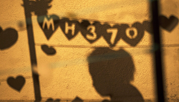 La sombra de una persona pasa ante uno de los carteles que recuerdan a las víctimas del vuelo en Kuala Lumpur