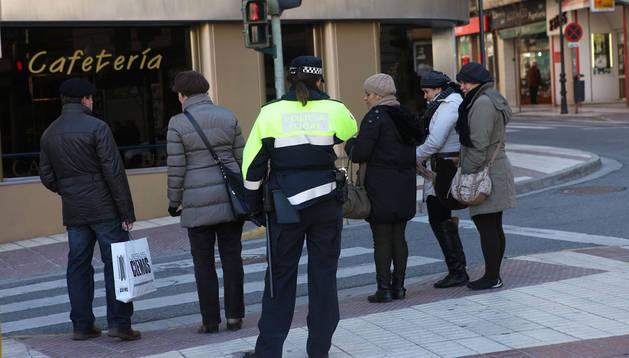 Una agente vigila el paso de varios peatones en Tudela