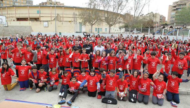 Los alumnos del colegio público Griseras de Tudela posan con sus camisetas rojillas juntos a los jugadores de la primera plantilla Sisi y Gato Silva en el patio del centro
