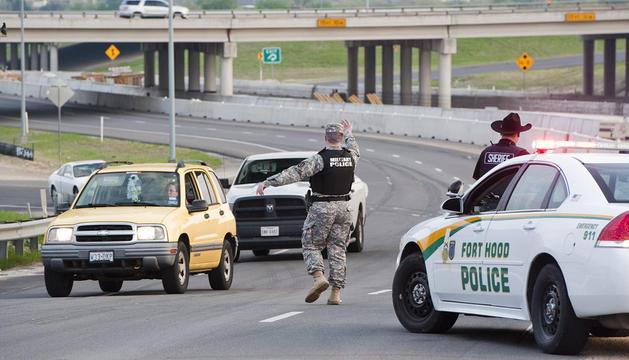 Un policía militar dirige el tráfico cerca a la base militar asegurada de Fort Hood tras el tiroteo.