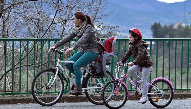 Una mujer y una niña pasean en bicicleta