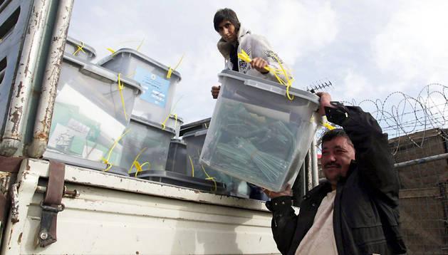 Dos trabajadores cargan urnas con votos en un camión