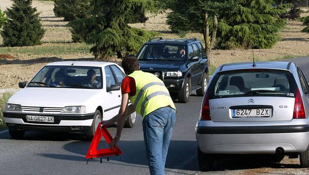 Una persona señaliza la vía tras un accidente