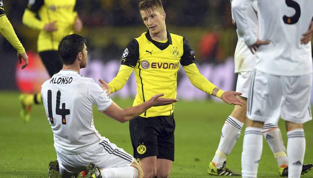 Marco Reus conversa con Xabi Alonso durante el partido