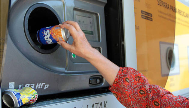 Una mujer recicla una lata.