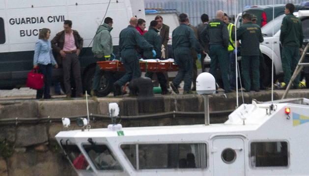 Varias personas trasladan el cuerpo de Alexander Nketiah, de origen ghanés, uno de los dos marineros del Mar de Marín que seguían desaparecidos, tras ser recuperado este miércoles por los buceadores de la Guardia Civil