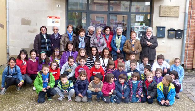 Los niños posan con algunas de las mujeres del pueblo que han dado pie a la exposición fotográfica.
