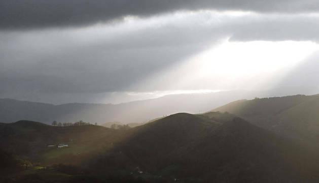 El sol, asomando tímidamente entre los montes del Pirineo navarro, en el valle de Baztan