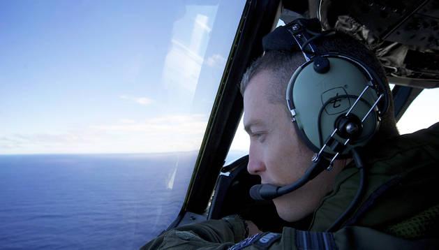 El capitán Tim McAlevey, de la Marina de Nueva Zelanda, observa desde un avión el océano Índico