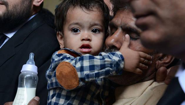 El bebé acusado en brazos de su padre