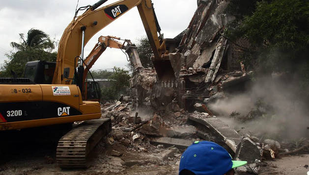 Maquinaria pesada derriba los restos de dos edificios afectados por el terremoto en Managua
