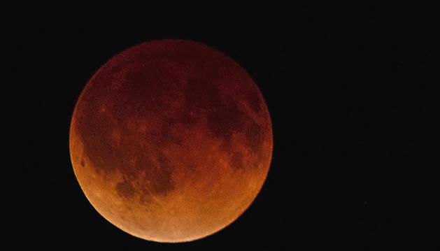 La Luna se tiñe de rojo y naranja durante el eclipse lunar total visto desde Kansas (Estados Unidos)