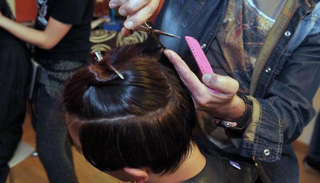 Un peluquero realiza un corte de pelo con tijeras