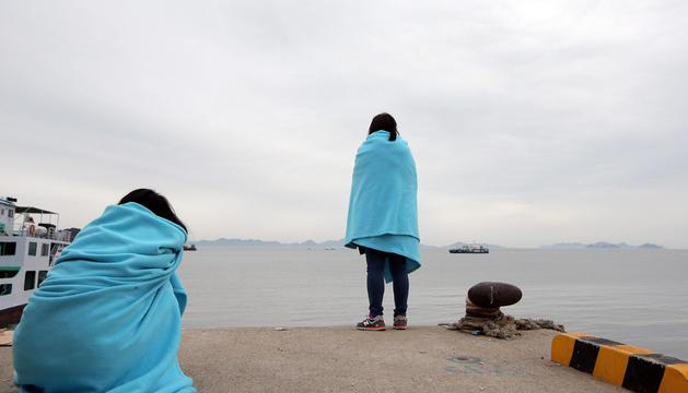 Familiares de los desaparecidos en el naufragado ferri Sewol esperan en el puerto.