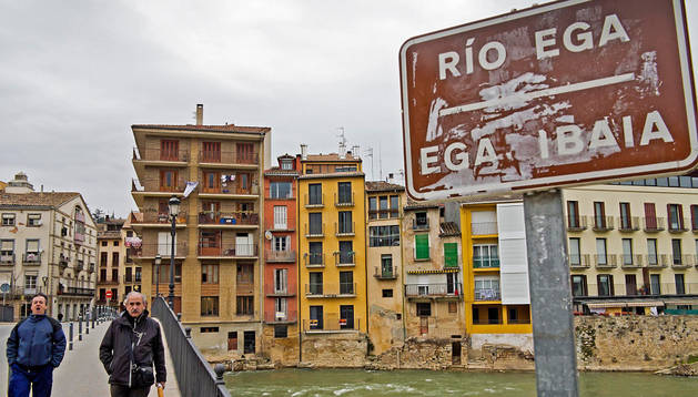 Dos personas caminan por el área peatonal del puente del Azucarero que libra el paso del río Ega por Estella. Archivo